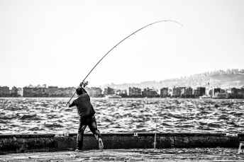 grayscale photography of man holding a fishing rod near body of water