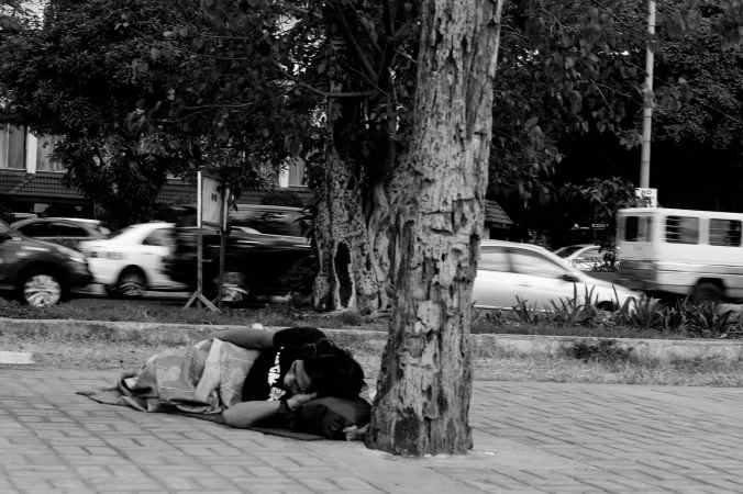 grayscale photo of man lying beside tree